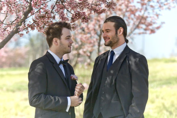 Two men dressed for a wedding stand under a blooming cherry blossom tree in a green meadow.
