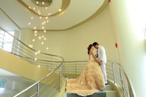 man and woman standing on staircase near chandelier