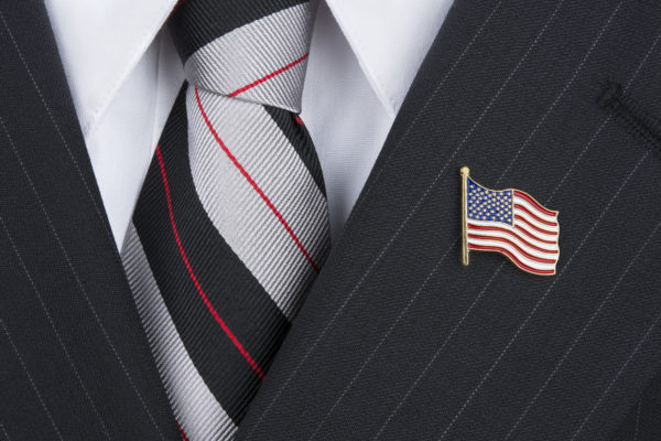 A politician wearing an American flag lapen pin symbolizes patriotism.