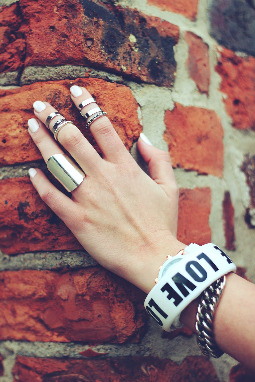 wearing rings and jewelry on left hand against brick wall